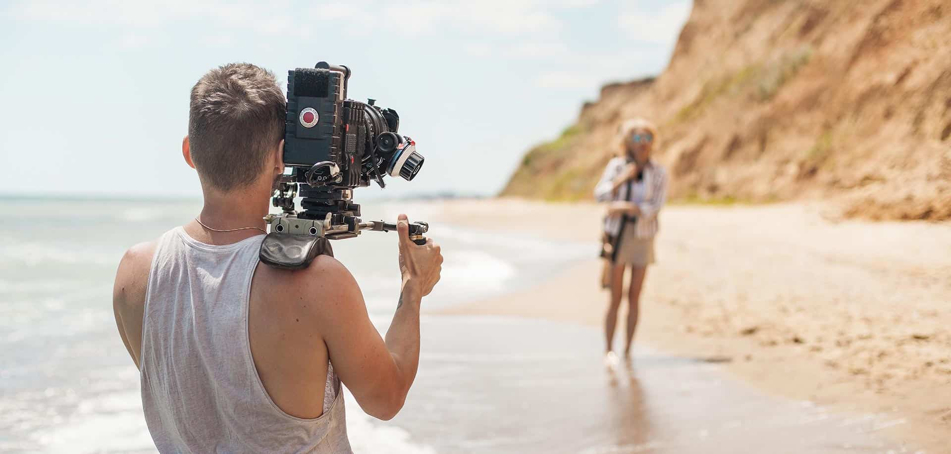 filmmaker is making video with the woman at the beach.
